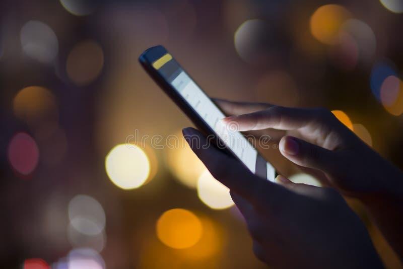 Frau, die ihren Handy, Stadtskylinenachtlicht backgro verwendet stockfotos