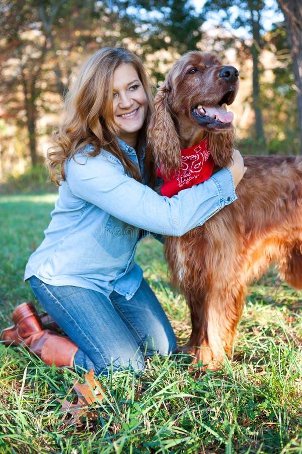 Frau, die ihren Hund umarmt lizenzfreie stockfotografie