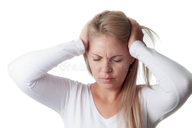 Frau, die ihren Kopf lokalisiert auf weißem Hintergrund hält Kopfschmerzen lizenzfreie stockfotografie