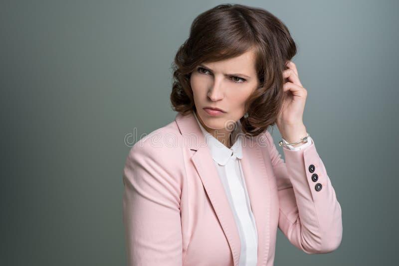 Frau, die ihren Kopf mit einem verwirrten Stirnrunzeln verkratzt lizenzfreie stockfotografie