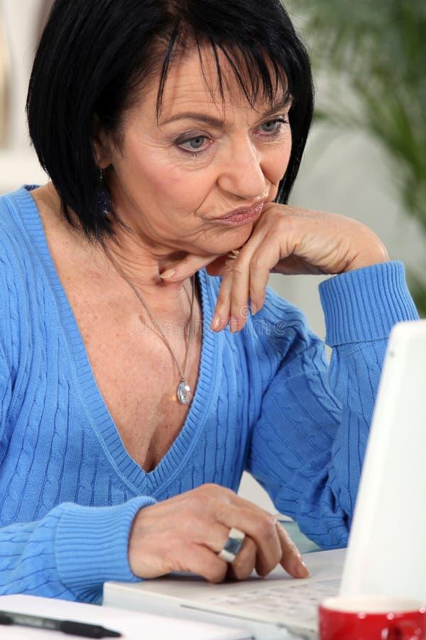 Frau, die ihren Laptop betrachtet lizenzfreie stockfotografie