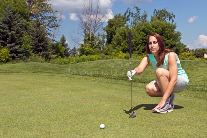 Frau, die ihren Schlag auf dem Golfgrün ausrichtet stockfotografie