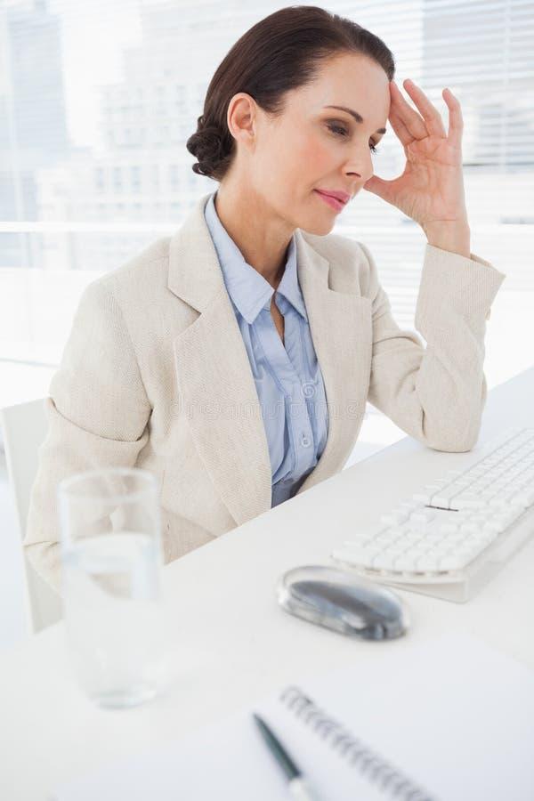 Frau, die ihren wunden Kopf massiert lizenzfreie stockfotografie