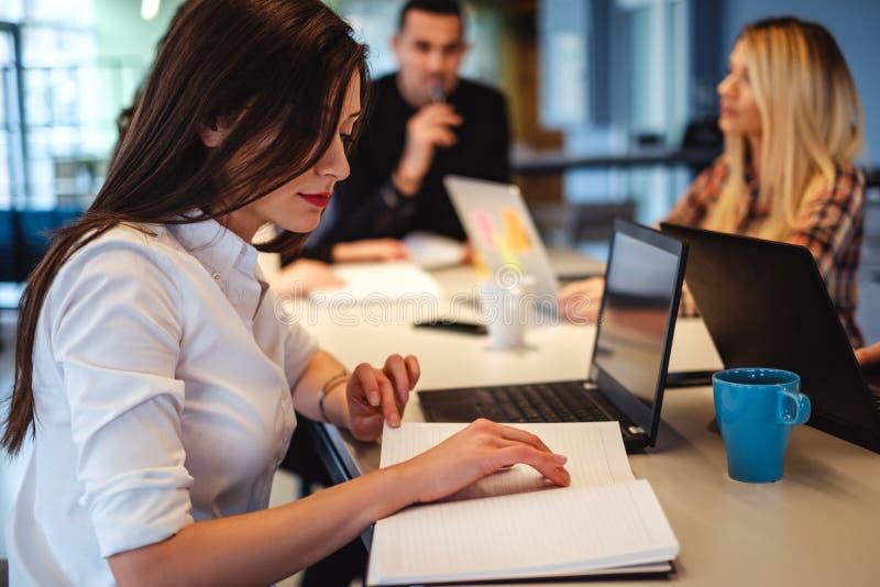 Frau, die ihren Zeitplan im Büro betrachtet lizenzfreies stockfoto