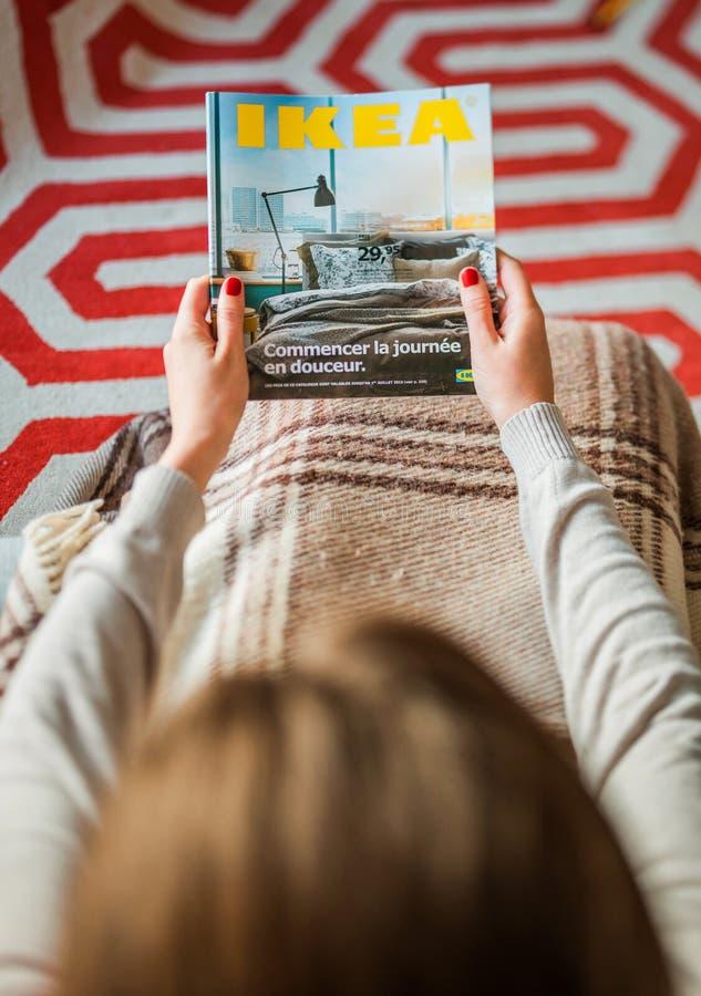 Frau, die IKEA-Katalogabdeckung vor Einrichtungshaus liest lizenzfreies stockbild