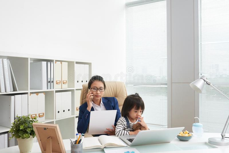 Frau, die im Büro mit reizend Mädchen arbeitet stockfotografie