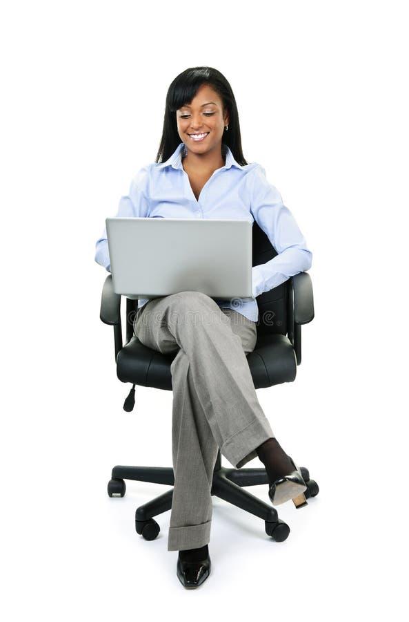 Frau, die im Bürostuhl mit Computer sitzt lizenzfreie stockfotos