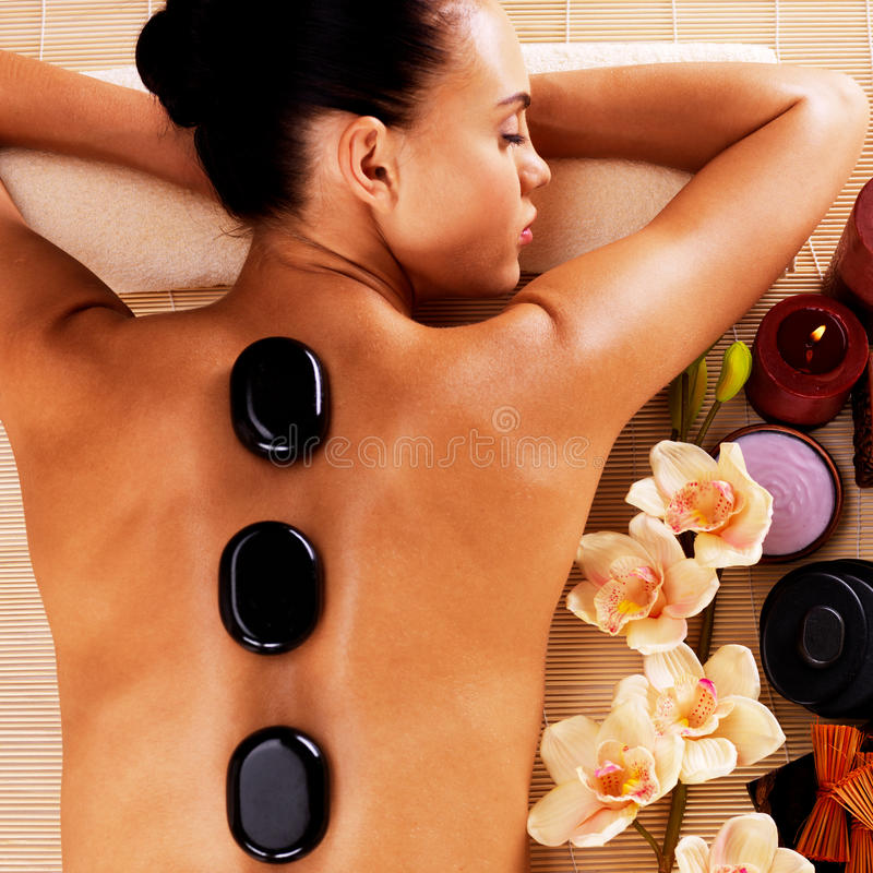 Frau, die im Badekurortsalon mit heißen Steinen auf Körper sich entspannt lizenzfreie stockfotos