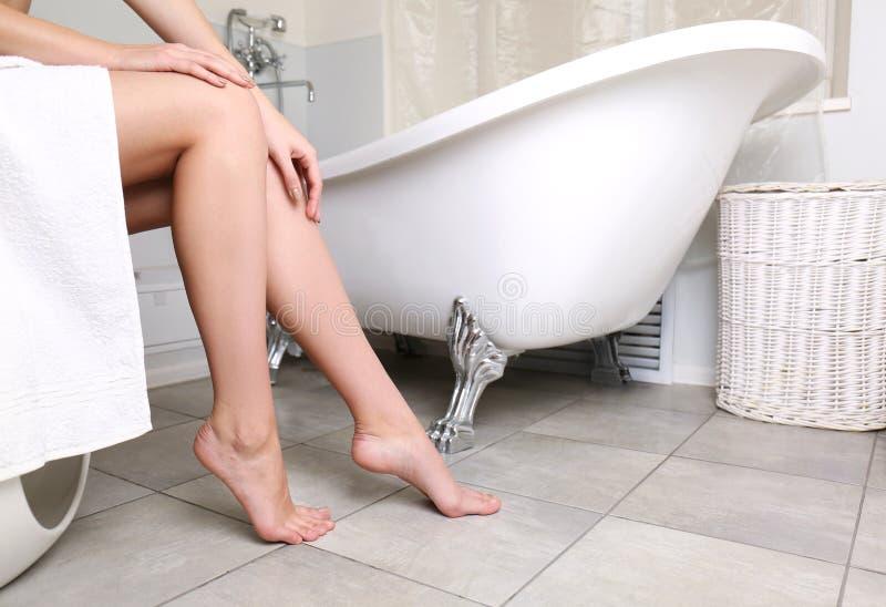 Frau, die im Badezimmer, Nahaufnahme von weiblichen Beinen sitzt stockbild