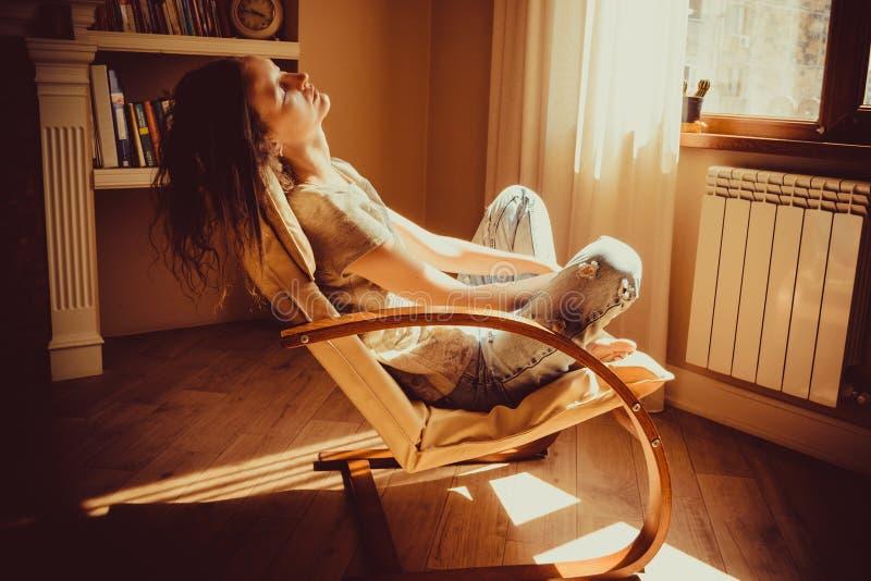 Frau, die im bequemen modernen Stuhl nahe Fensterheizkörper, Wohnzimmer sich entspannt und Nickerchen macht Warmes natürliches Li stockfotografie
