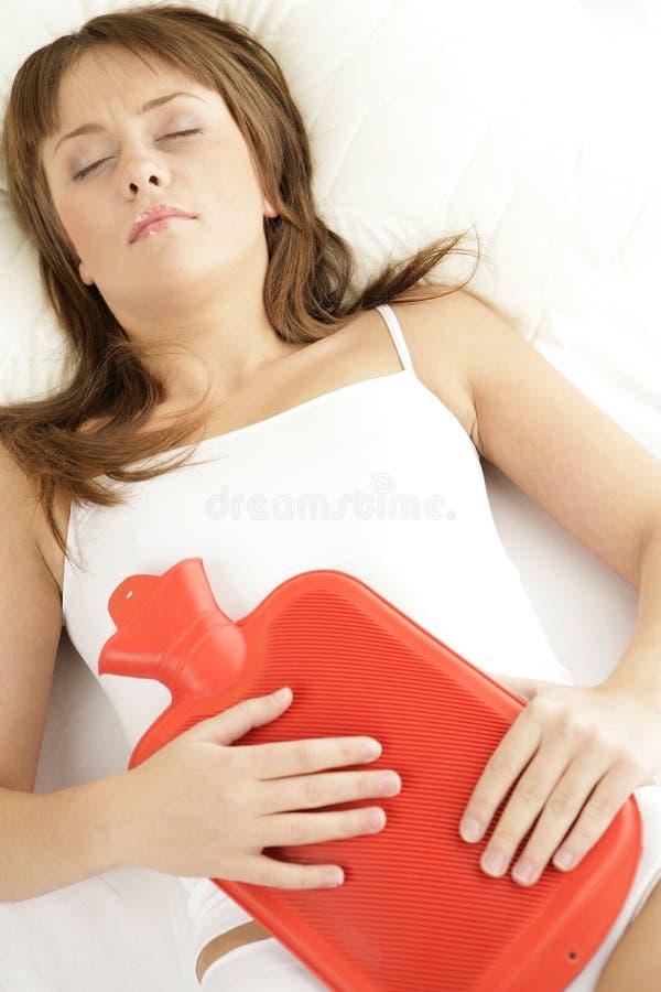 Frau, die im Bett mit Wärmflasche auf ihrem Magen liegt lizenzfreie stockfotografie