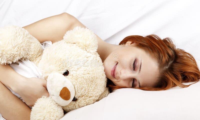 Frau, die im Bett mit weichem Spielzeug liegt. lizenzfreie stockfotos