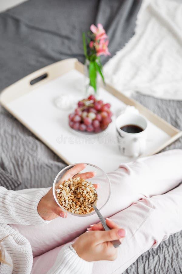Frau, die im Bett morgens frühstückt stockbild