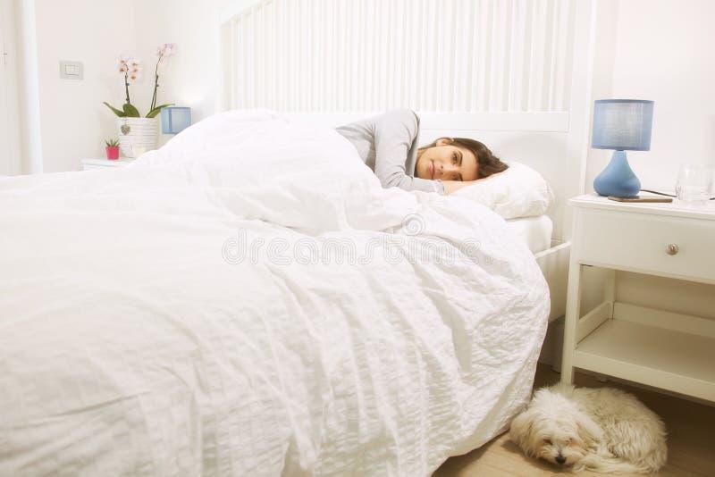 Frau, die im Bett nahe bei Hundeglücklicher schauender Kamera liegt lizenzfreies stockbild