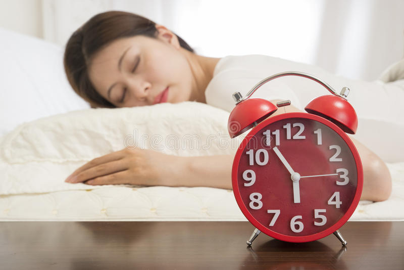 Frau, die im Bett neben Wecker schläft stockbild