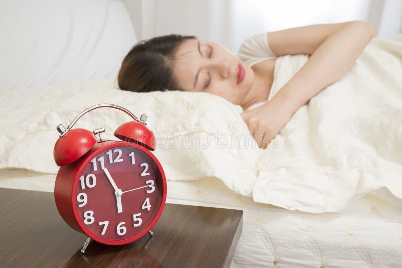 Frau, die im Bett neben Wecker schläft stockfotografie