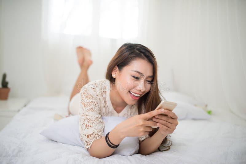 Frau, die im Bett sich entspannt und Musik, entspannend in ihrem Li hört lizenzfreies stockbild