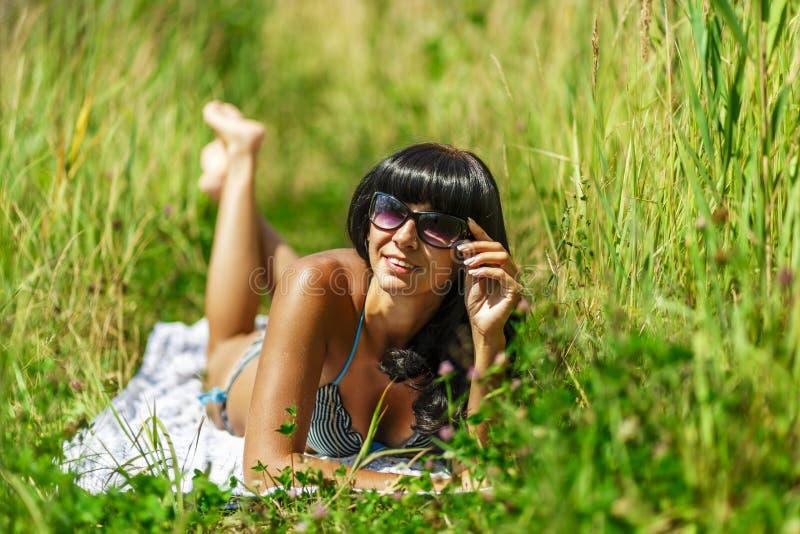 Frau, die im Bikini ein Sonnenbad nimmt lizenzfreie stockbilder