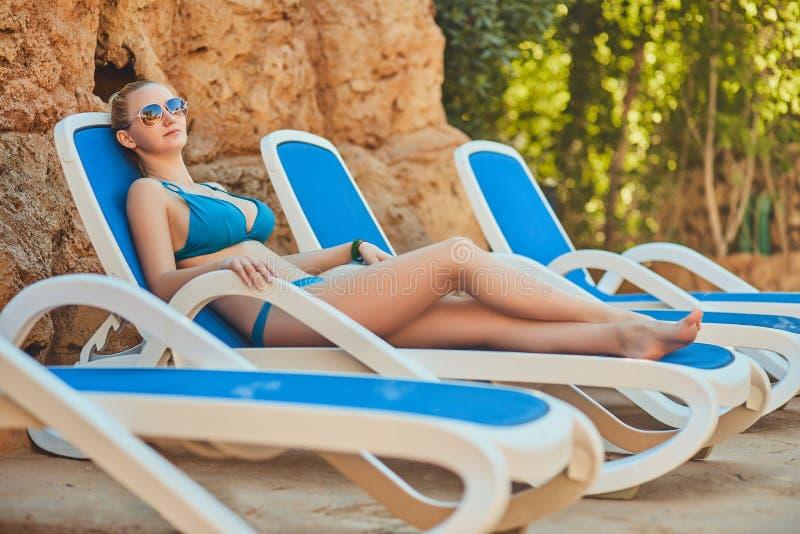 Frau, die im Bikini am tropischen Erholungsort ein Sonnenbad nimmt Schönheit, die auf Sonnenruhesessel liegt stockbild