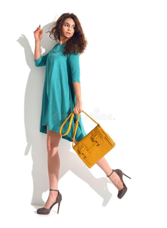 Frau, die im blauen tadellosen Modekörper-Kleiderstoff mit braunem ha aufwirft stockbild