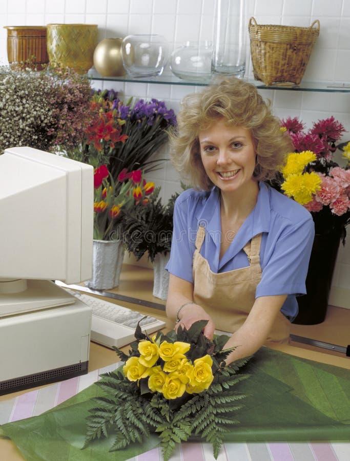 Frau, die im Blumensystem arbeitet stockbilder