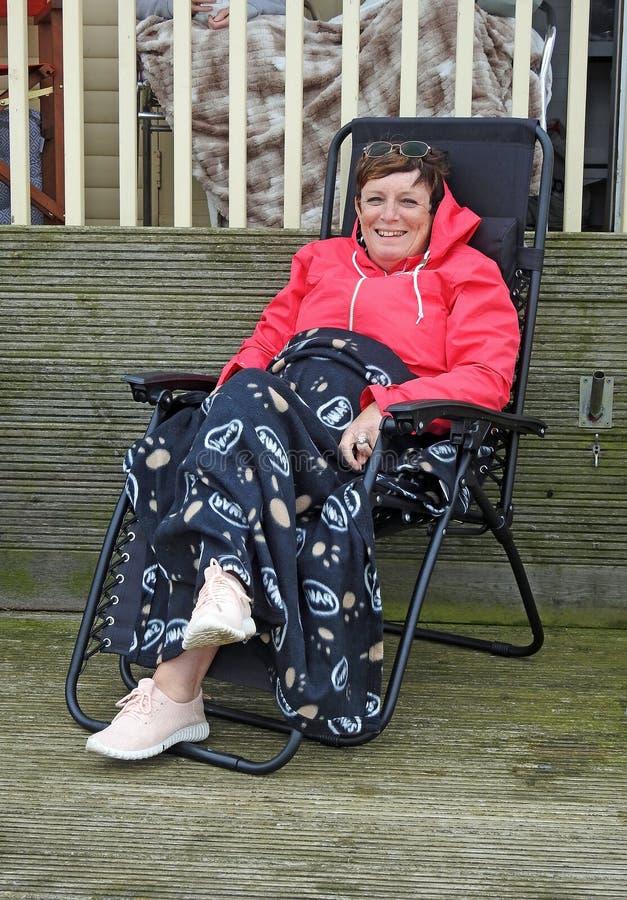 Frau, die im deckchair auf Feiertagsstrandhütte sich entspannt stockfotografie