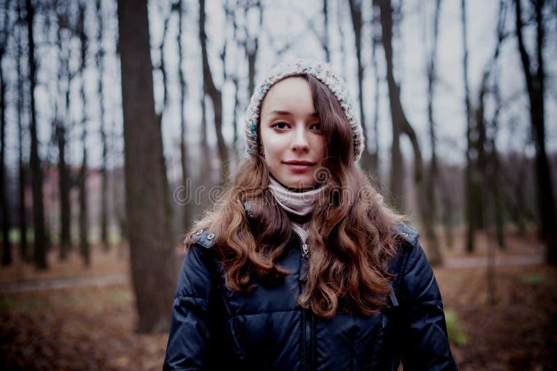 Frau, die im dunklen kalten Waldhintergrund steht stockbild