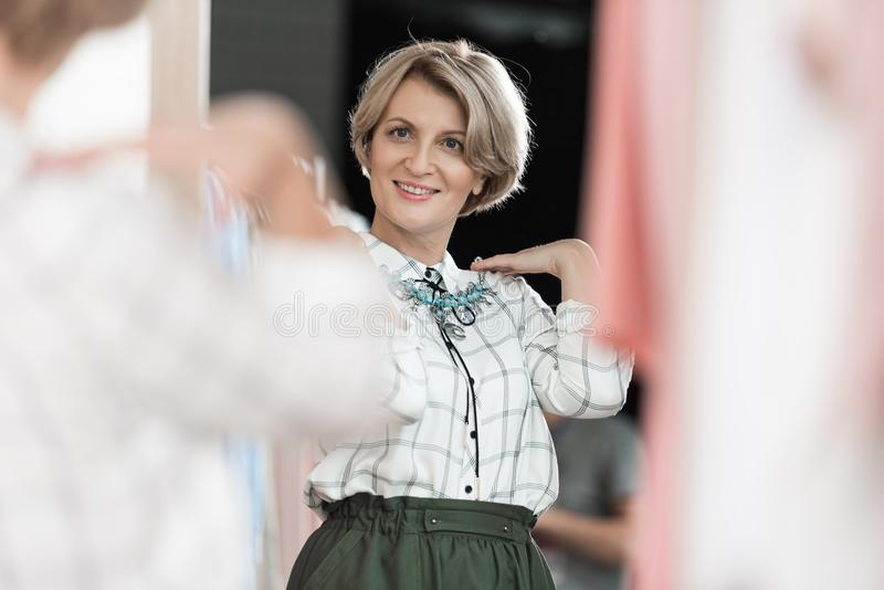 Frau, die im Geschäft auf einer Halskette in der Front versucht stockfoto