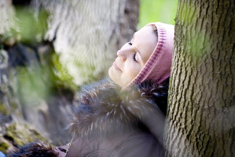 Frau, die im Holz sich entspannt stockfoto