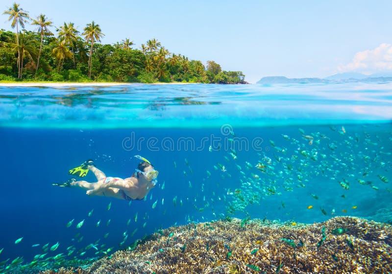 Frau, die im klaren tropischen Wasser schnorchelt lizenzfreie stockbilder