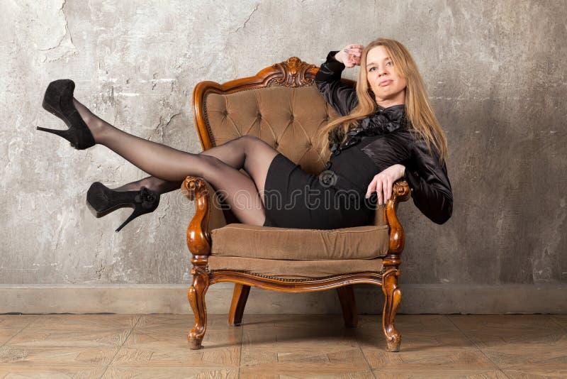Frau, die im Lehnsessel sitzt lizenzfreies stockfoto