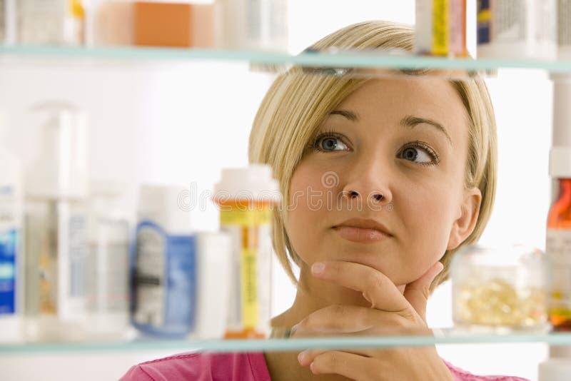 Frau, die im Medizin-Kabinett schaut lizenzfreie stockbilder