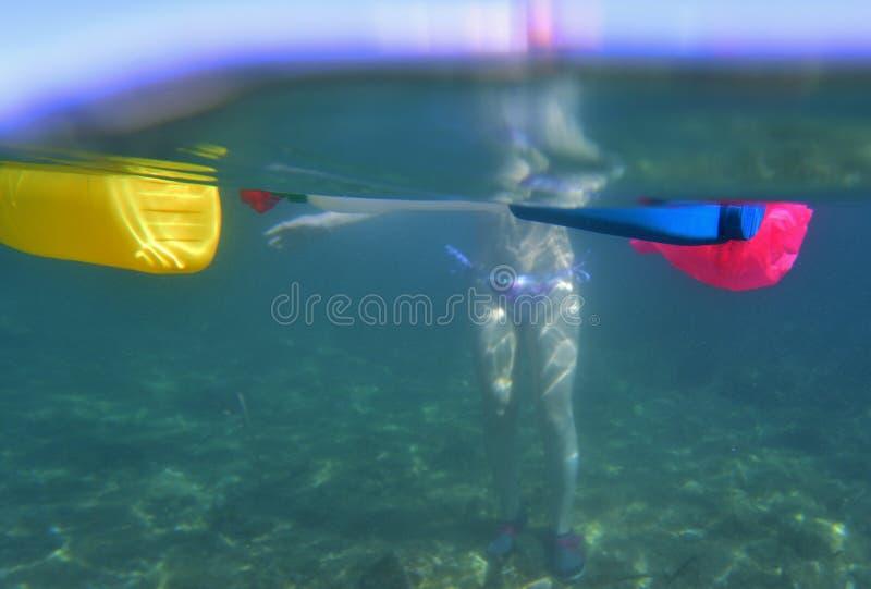 Frau, die im Meer mit Plastik badet lizenzfreie stockfotos