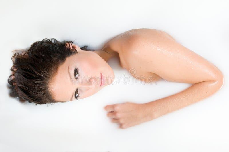 Frau, die im Milchbad sich entspannt lizenzfreie stockfotos