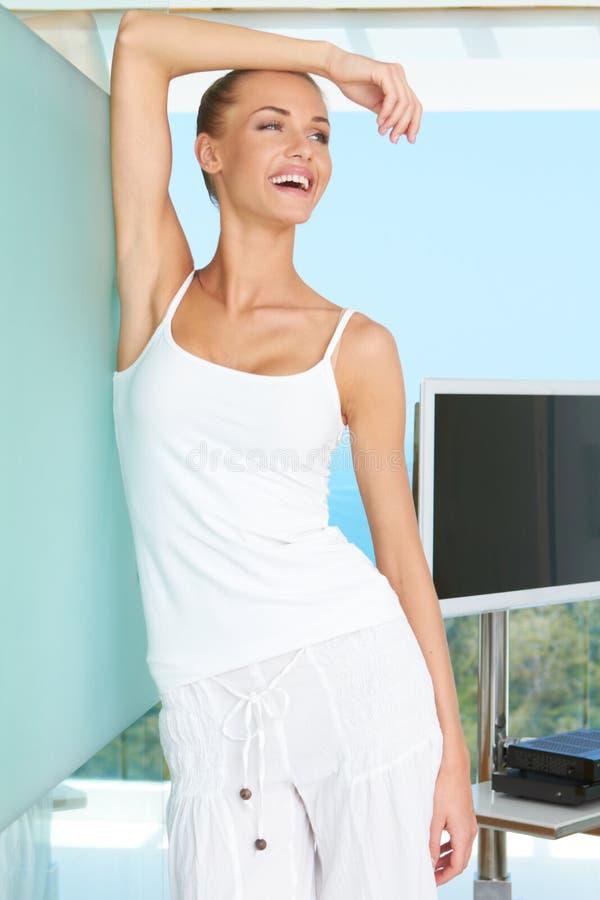 Frau, die im modernen Wohnzimmer lacht lizenzfreie stockfotografie