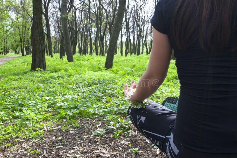 Frau, die im Park, in der Harmonie und in der Gesundheit meditiert stockbilder