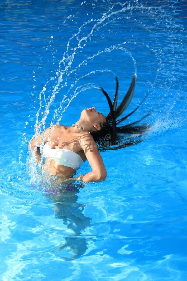 Frau, die im Pool sich entspannt stockfotos