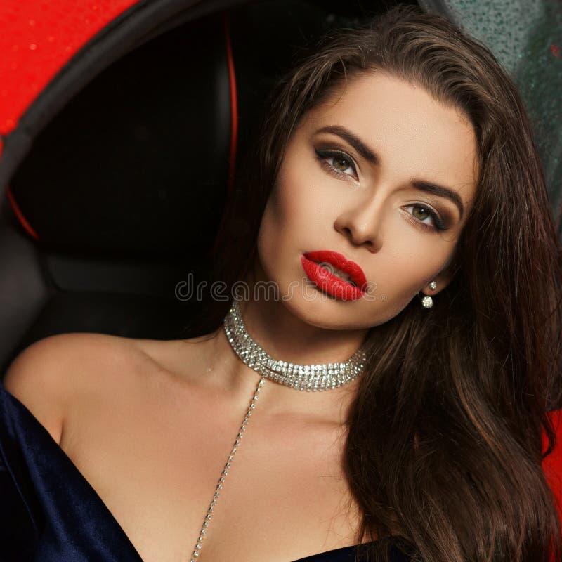 Frau, die im roten Auto sitzt stockfotos