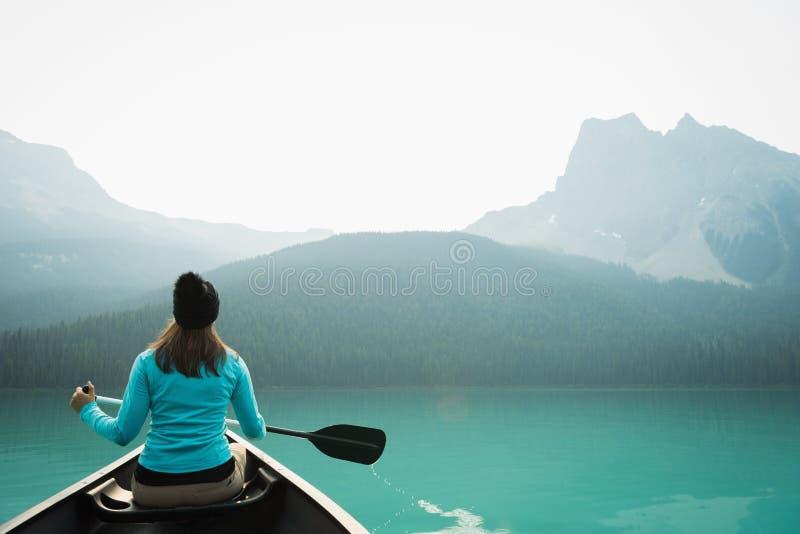 Frau, die im See Kayak fährt lizenzfreies stockfoto