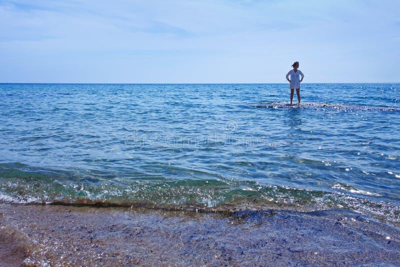 Frau, die im seichten Wasser des Meeres steht lizenzfreie stockfotos