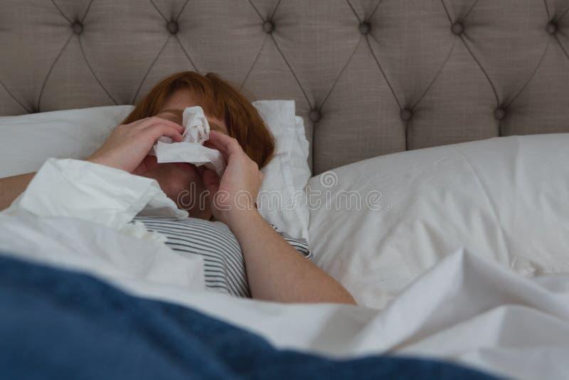 Frau, die im Seidenpapier im Schlafzimmer niest lizenzfreies stockbild