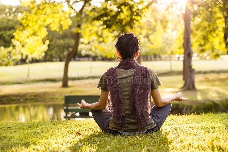 Frau, die im Sonnenlicht im Sommerpark meditiert lizenzfreies stockbild