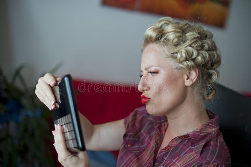 Frau, die im Spiegel schaut stockfotos