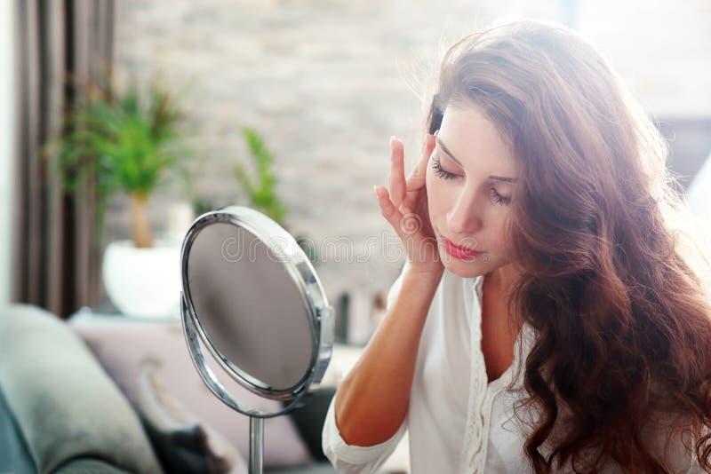 Frau, die im Spiegel schaut stockbilder