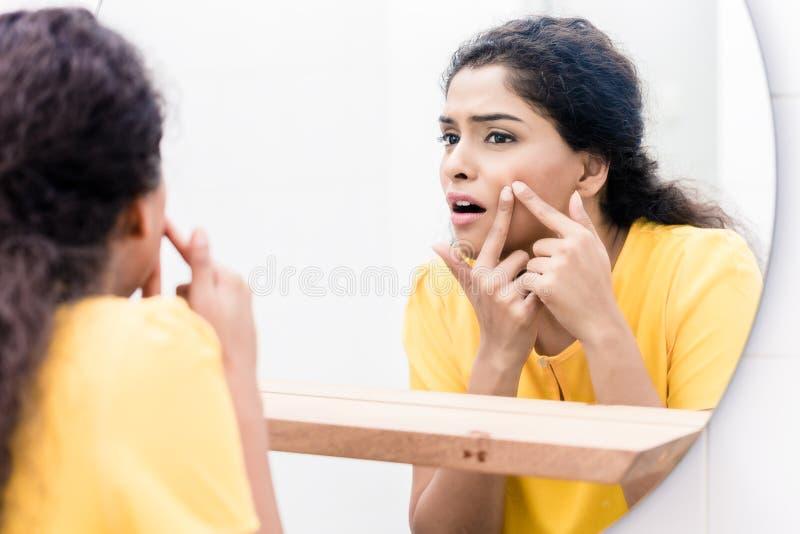 Frau, die im Spiegel zusammendrückt Pickel schaut stockfoto