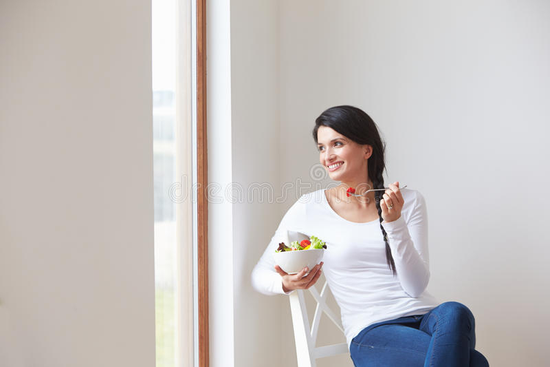 Frau, die im Stuhl isst Schüssel frische Frucht sitzt stockbild