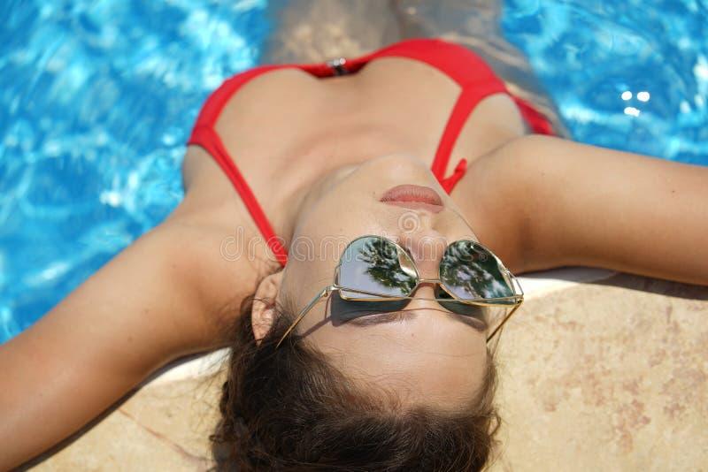 Frau, die im Swimmingpool sich entspannt stockfotografie