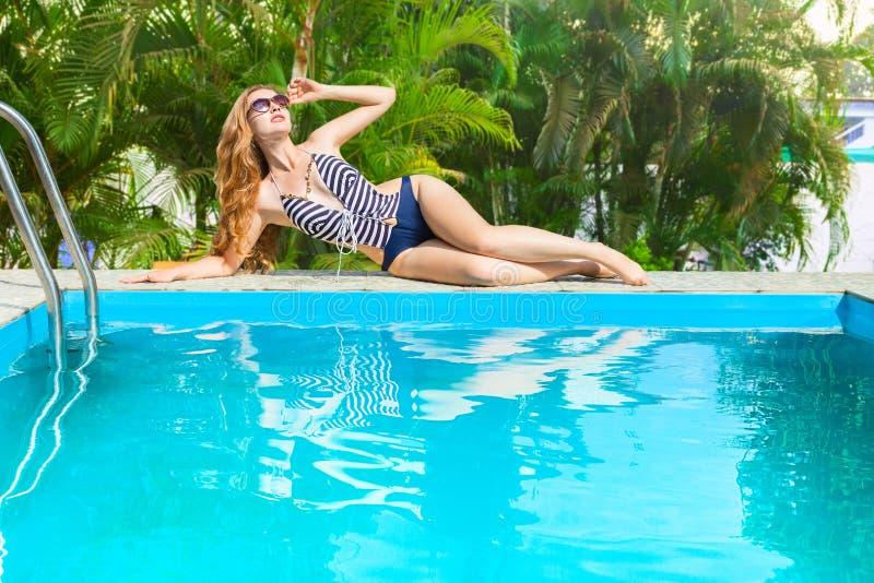 Frau, die im Swimmingpool sich entspannt stockfoto