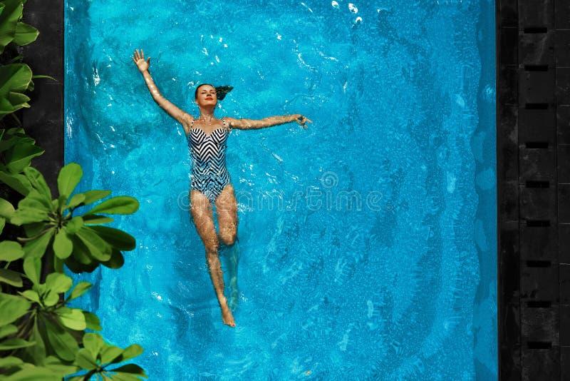 Frau, die im Swimmingpool-Wasser sich entspannt Sommerferienferien lizenzfreie stockfotos