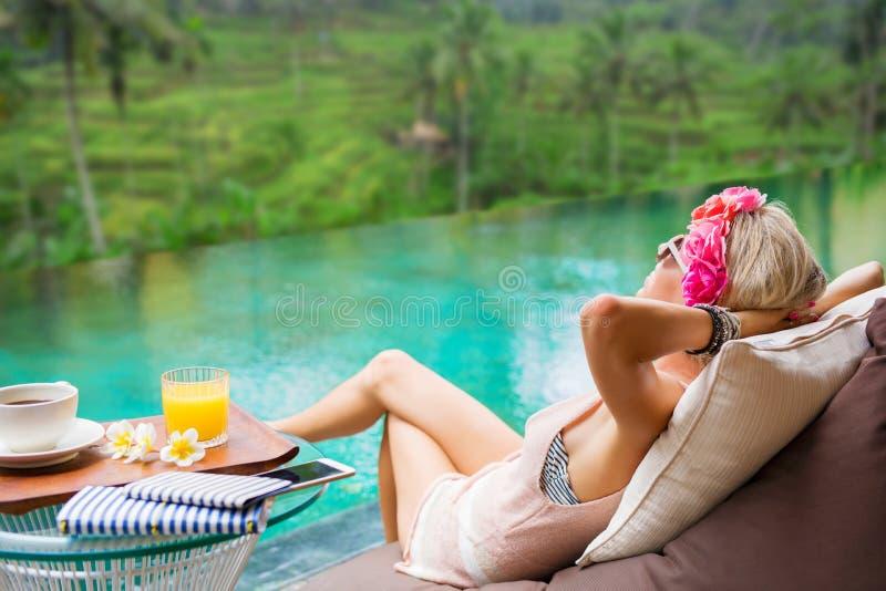 Frau, die im tropischen Landhaus sich entspannt stockbild